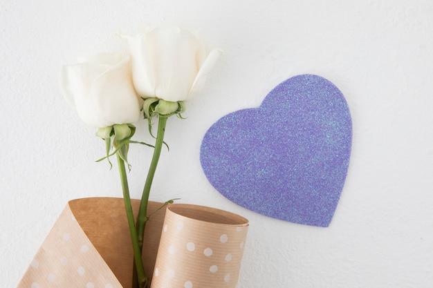 Flores rosas com coração de papel na mesa Foto gratuita