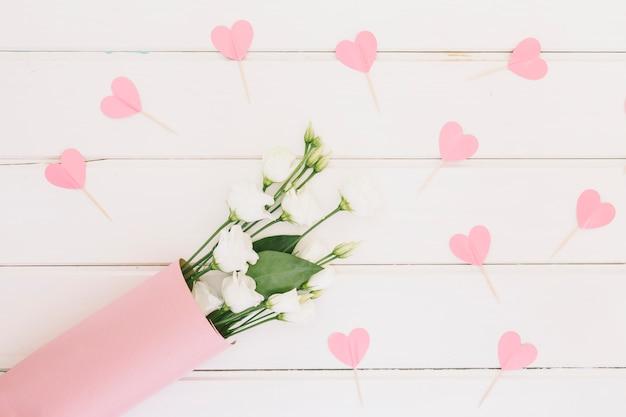 Flores rosas com corações de papel na mesa Foto gratuita