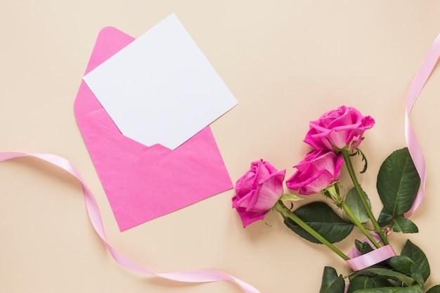 Flores rosas com papel no envelope Foto gratuita