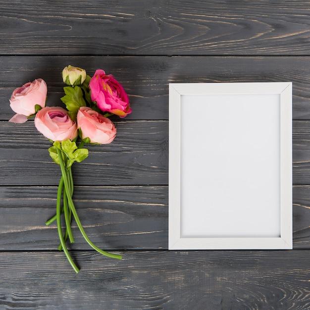 Flores rosas cor de rosa com moldura em branco na mesa de madeira Foto gratuita