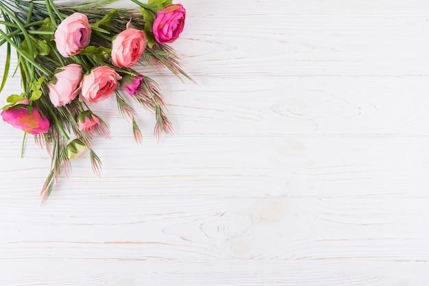 Flores rosas cor de rosa com ramos de plantas na mesa de madeira Foto gratuita