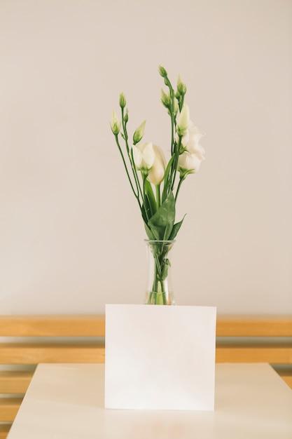 Flores rosas em vaso com papel em branco Foto gratuita