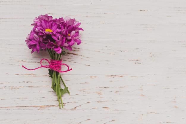 Flores Lilas Con Rosas Sobre Fondo: Flores Roxas Amarradas Na Superfície De Madeira Branca
