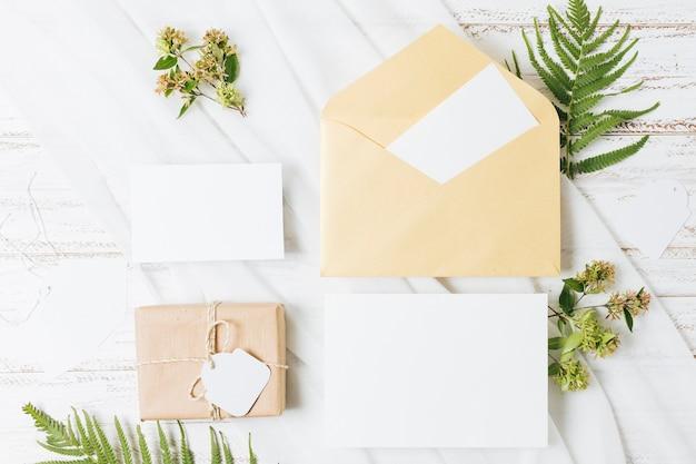 Flores; samambaia; caixa de presente embrulhada; cartão; envelope e cachecol na mesa de madeira Foto gratuita