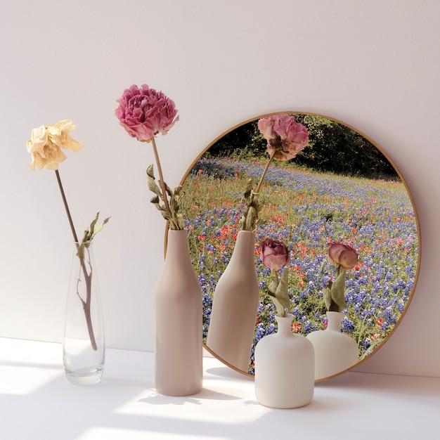 Flores secas em vasos mínimos perto de um espelho redondo Foto gratuita