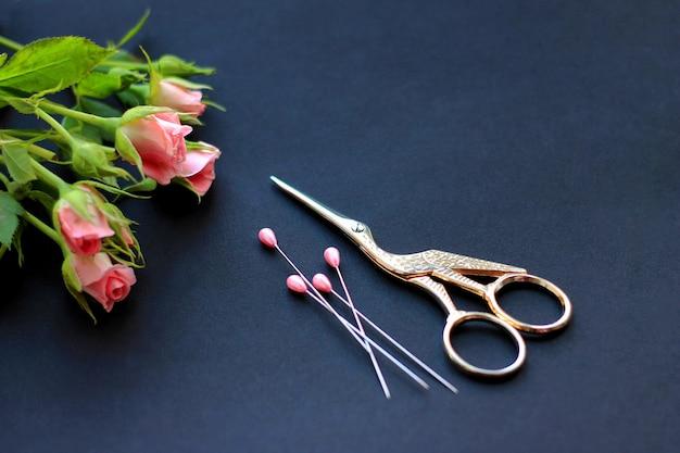 Flores, tesoura para costura e alfinetes em um fundo escuro o conceito de parabéns no feriado e bordado Foto Premium
