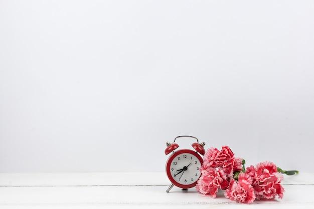 Flores vermelhas de cravo e despertador vermelho na superfície de madeira branca Foto gratuita