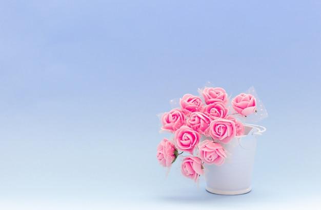 Flores vermelhas em um balde de brinquedo branco sobre um fundo azul ou roxo, flores para o feriado Foto Premium