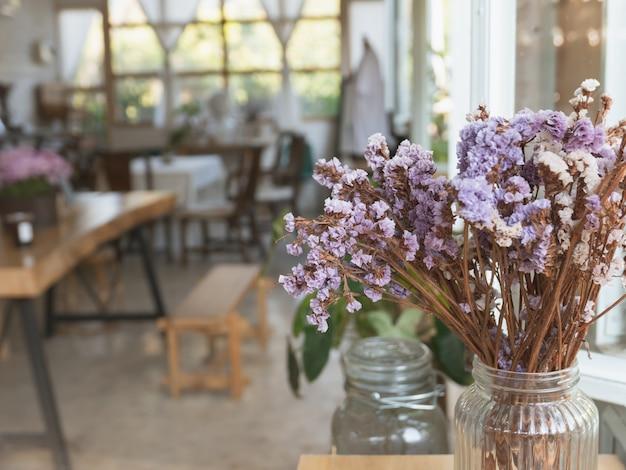 Flores vintage na mesa de madeira no café Foto Premium