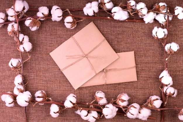Floresça com cápsulas macias de algodão seco e caixas de presente sobre estopa marrom áspera. Foto Premium