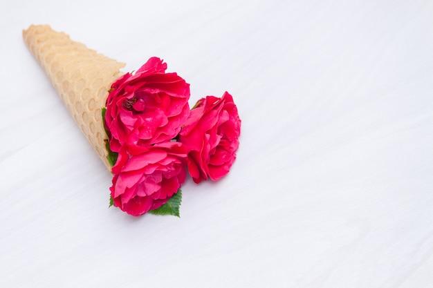 Floresce rosas vermelhas em um cone de waffle em fundo branco de madeira. vista plana leiga, superior, fundo floral. Foto Premium