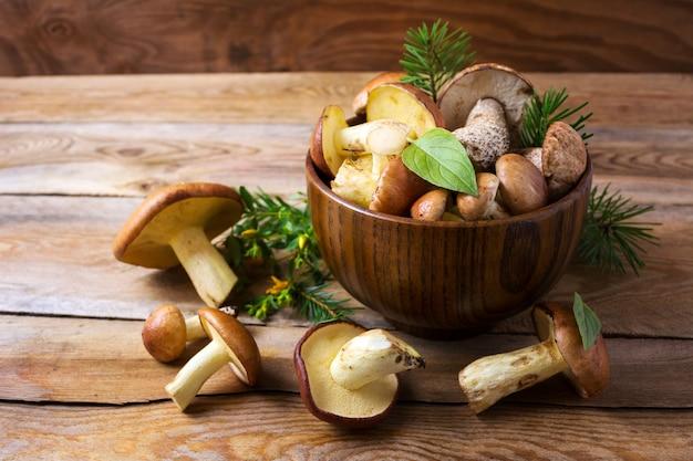 Floresta colhendo cogumelos na tigela de madeira Foto Premium