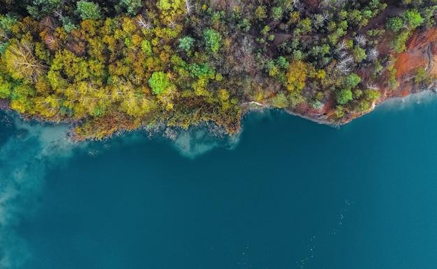 Floresta densa vista aérea no outono perto do lago água azul Foto Premium