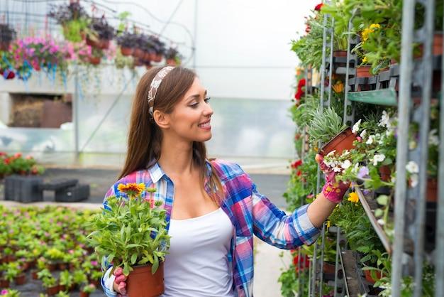 Florista arrumando flores em centro de jardim Foto gratuita