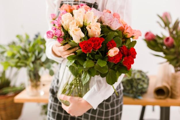 Florista de close-up, segurando o frasco com flores Foto gratuita
