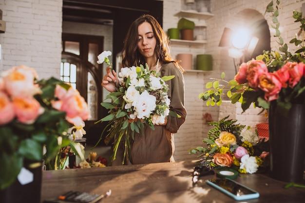 Florista de mulher em sua própria loja floral, cuidando de flores Foto gratuita