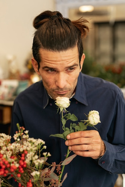 Florista experiente cheirando rosas brancas Foto gratuita