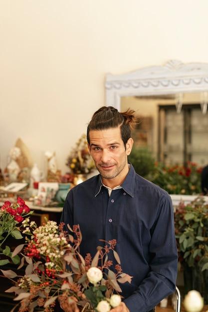 Florista experiente em uma loja de flores Foto gratuita