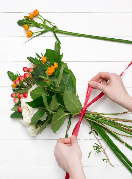 Florista feminina fazendo lindo buquê na loja de flores Foto gratuita
