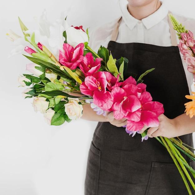Florista feminina mão segurando o monte de flores brancas e vermelhas Foto gratuita