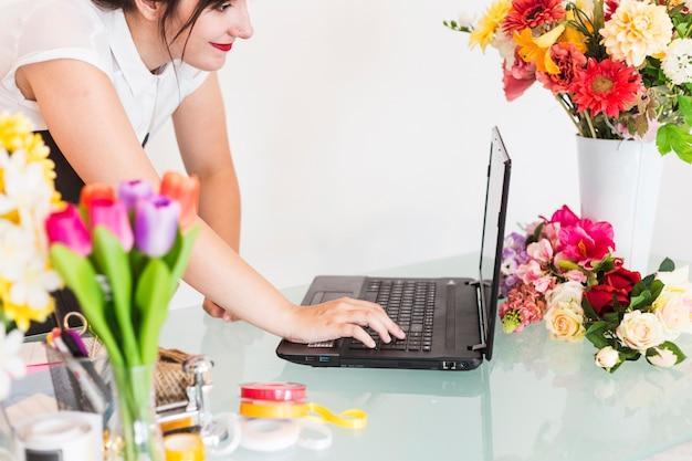 Florista feminina usando o laptop na mesa Foto gratuita