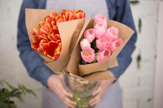 Florista masculina segurando rosa e um buquê de tulipas laranja embrulhado em papel Foto gratuita