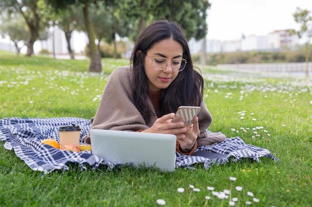 Focada garota séria usando gadgets no parque Foto gratuita