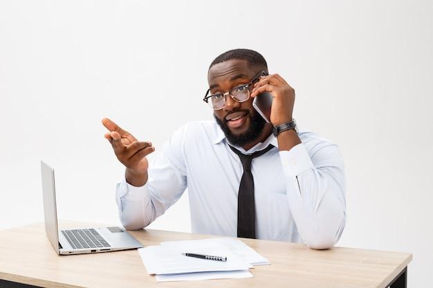 Focada gerente de escritório afro-americano sentado no escritório com laptop, lendo documentos importantes com expressão confusa e segurando a cabeça com a mão Foto Premium