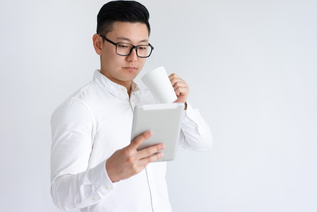 Focada homem asiático usando tablet e bebendo café Foto gratuita
