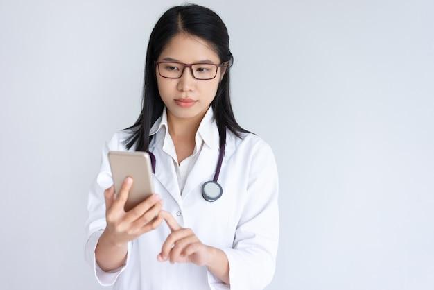 Focada jovem médico feminino usando smartphone Foto gratuita