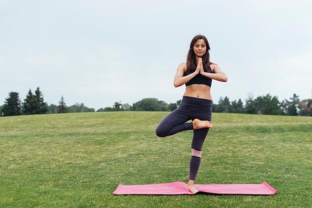 Focada mulher fazendo ioga ao ar livre Foto gratuita