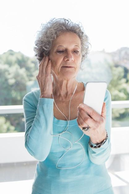 Focada sênior senhora usando telefone e fones de ouvido Foto gratuita