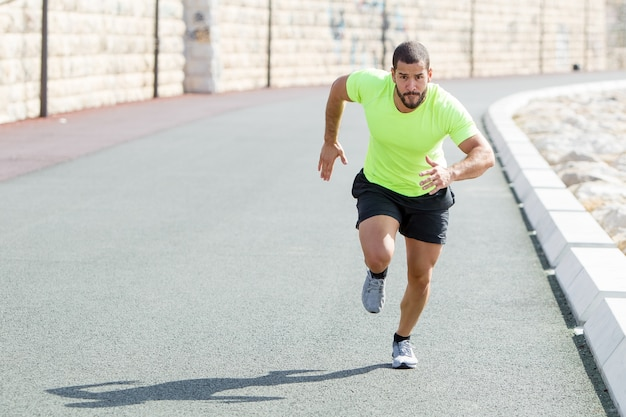 Focado forte homem desportivo correndo rápido na estrada Foto gratuita