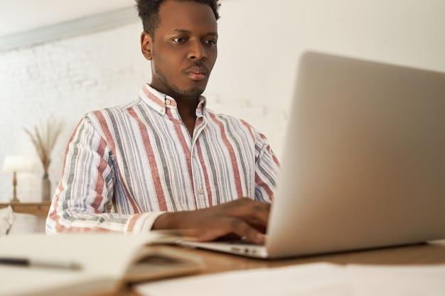 Focado jovem africano do sexo masculino fazendo tarefas remotas freelance em casa, procurando informações usando wi-fi de alta velocidade. Foto gratuita