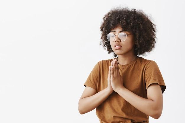 Focado relaxado e calmo jovem atraente de pele escura usando óculos com penteado afro em pé meio virado para a esquerda com olhos fechados gesto de namaste ou mãos em oração meditando Foto gratuita