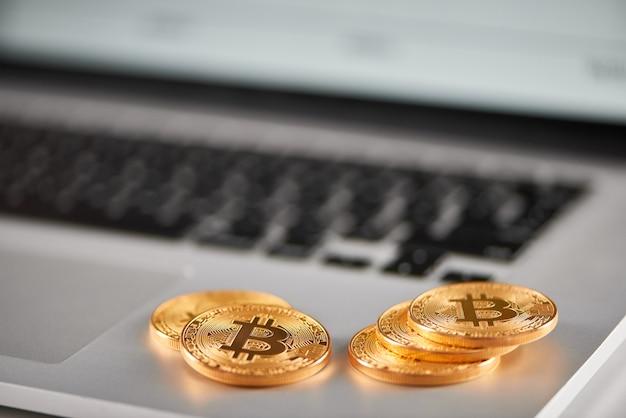 Foco afiado nos bitcoins dourados colocados no portátil de prata com carta financeira borrada em sua tela. Foto Premium