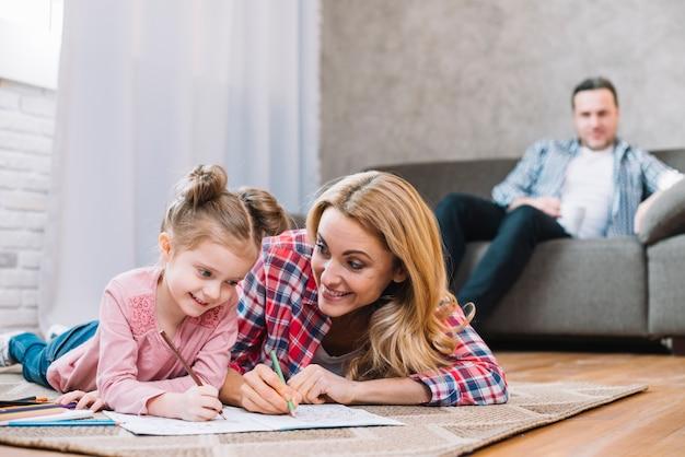 Foco borrado pai olhando sua esposa e filha enquanto desenhando no livro Foto gratuita