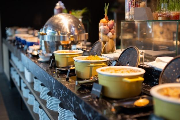 Foco selecionado do macarronete de ovos ateado fogo em um po na linha do bufete para o café da manhã. Foto Premium