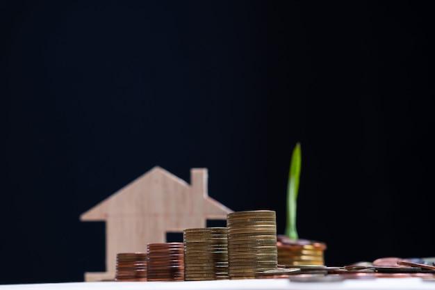 Foco seletivo da pilha de moedas de dinheiro com modelo de casa turva e fundo escuro Foto Premium