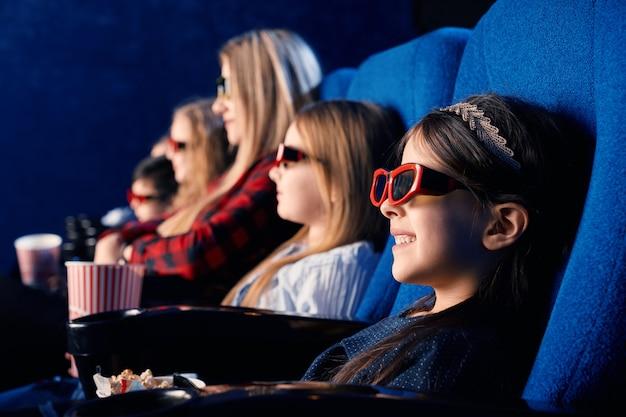 Foco seletivo de criança rindo usando óculos 3d, comendo pipoca e assistindo filme engraçado. menina bonitinha curtindo o tempo com os amigos no cinema Foto gratuita