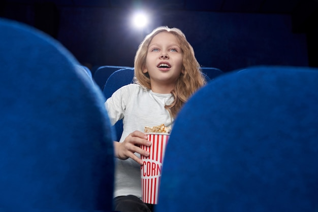 Foco seletivo de loira animada assistindo filme no cinema Foto gratuita