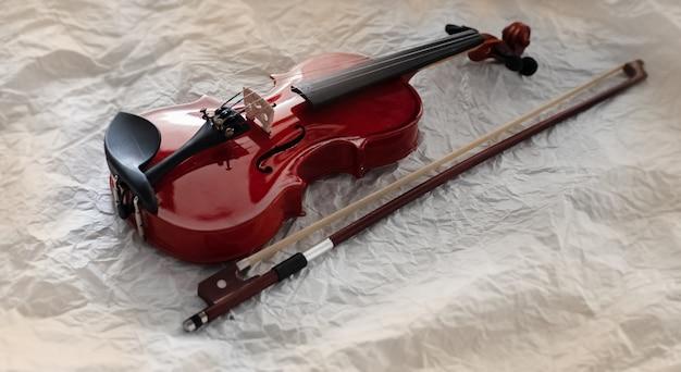 Foco seletivo de violino de madeira colocar ao lado do arco Foto Premium