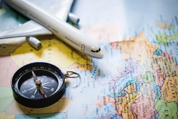 Foco seletivo do turista em miniatura sobre a bússola sobre o mapa com avião de brinquedo de plástico, fundo abstrato para o conceito de viagem. Foto gratuita