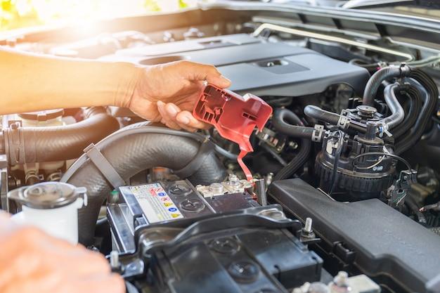 Foco seletivo, mão de homem técnico, verificando a bateria do carro no sistema de motor de carro Foto Premium