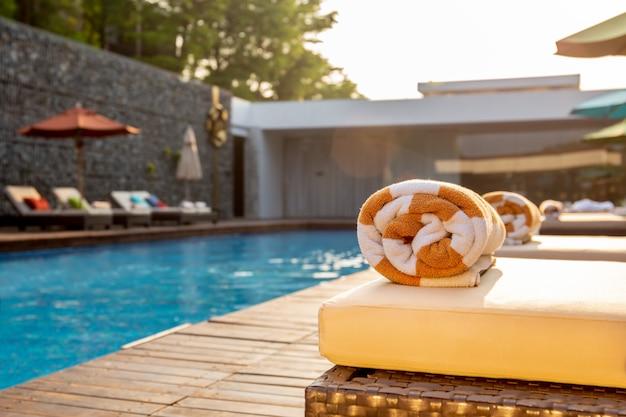 Foco seletivo na associação de toalha na cama da praia em torno da piscina no hotel. Foto Premium