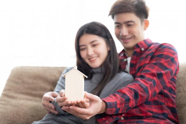 Foco seletivo no jovem casal da mão segurando a mini casa de madeira no sofá no quarto Foto gratuita