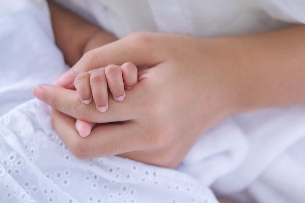 Foco suave das mãos e da mãe do bebê, nova família e proteção do bebê Foto Premium