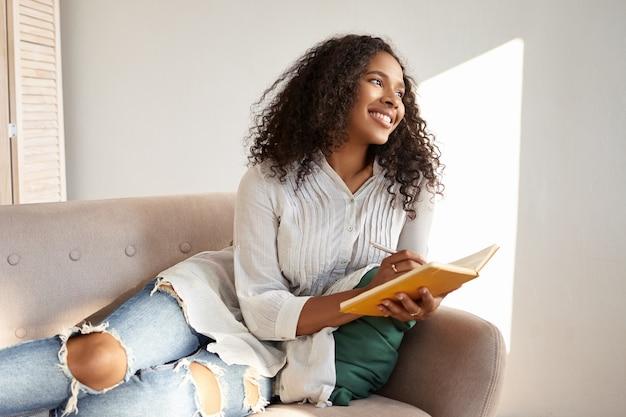 Fofa adorável aluna afro-americana com cabelo preto volumoso, aproveitando o tempo de lazer depois da faculdade, deitada no sofá com uma blusa e jeans rasgados elegantes, compartilhando pensamentos e ideias em seu diário Foto gratuita