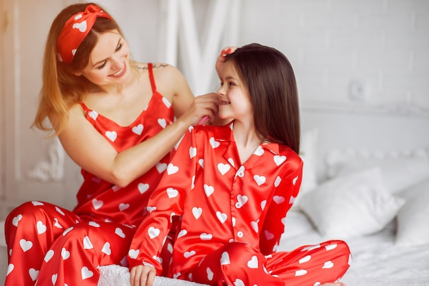 Fofa mãe e filha em casa de pijama Foto gratuita
