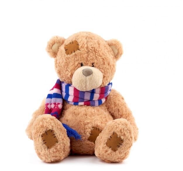 Fofo urso de pelúcia marrom com manchas em um cachecol de malha colorido Foto Premium